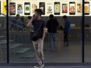 man_using_iphone_in_front_of_apple_store_ap