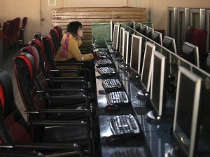 A woman uses a computer in an internet cafe in Shanghai