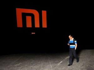 man checks mobile walks past logo xiaomi