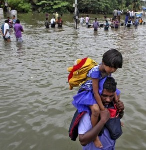 A man carries a girl through a flooded road in Chennai