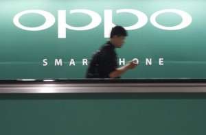 File photo of a commuter using his mobile phone passing an advertisement of Chinese smartphone maker Oppo at a train station in Singapore