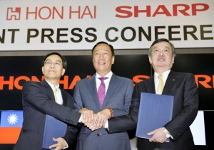 Founder and Chairman of Taiwan's Foxconn shakes hand with the company Vice Chairman and Japan's Sharp Corp Chief Executive at their joint news conference in Sakai
